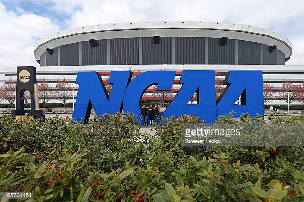 Fans stand next to a giant NCAA logo outside of the stadium on the practice day prior to the NCAA Men's Final Four at the Georgia Dome on April 5,...