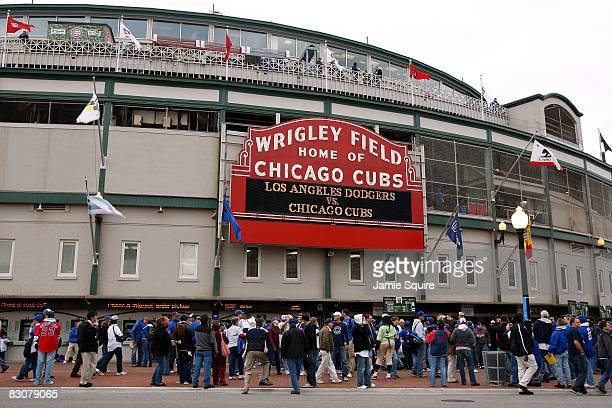 Fans stand outside Wrigley Field under the famous marquee which reads Los Angeles Dodgers vs Chicago Cubs prior to the Cubs hosting the Dodgers in...