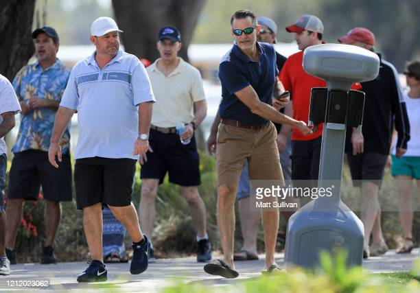 Fans stop at a hand sanitizer station during the first round of The PLAYERS Championship on The Stadium Course at TPC Sawgrass on March 12 2020 in...