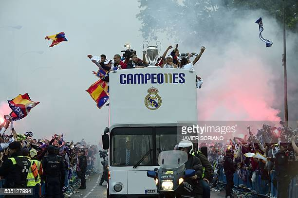 TOPSHOT Fans surround the bus as Real Madrid players hold up the trophy celebrating the team's win on Plaza Cibeles in Madrid on May 29 2016 after...