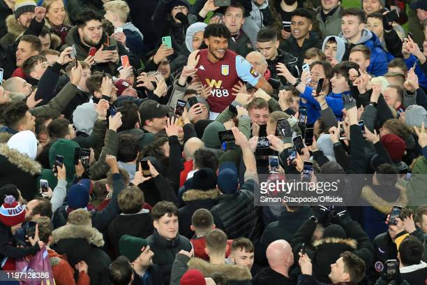 Fans swarm around Tyrone Mings of Villa as they celebrate victory after the Carabao Cup Semi Final match between Aston Villa and Leicester City at...