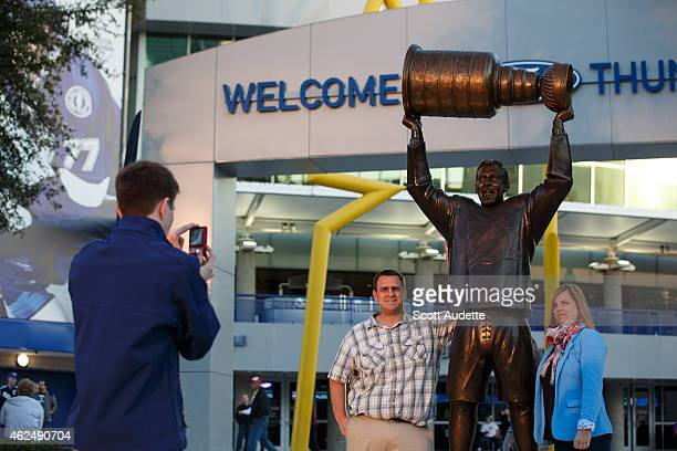 Fans take a photo with the statue Dave Andreychuk hoisting the Stanley Cup prior to the game between the Tampa Bay Lightning and the Detroit Red...