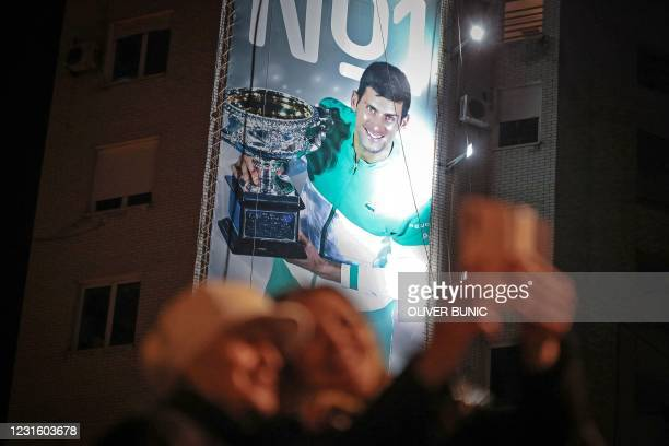 Fans take a selfie with a billboard in the background depicting Serbian tennis player Novak Djokovic in Belgrade on March 8, 2021. - Novak Djokovic...