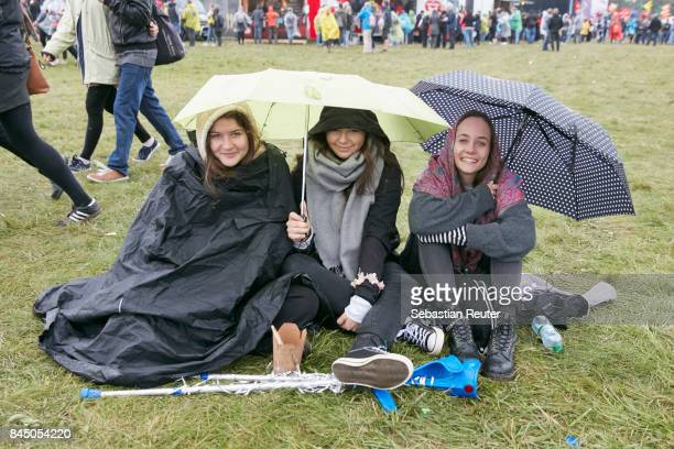 Fans take cover from the rain during the Lollapalooza Berlin music festival on September 9 2017 in DahlwitzHoppegarten Germany