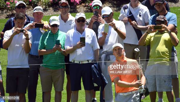 Fans take images of Jordan Spieth of the US as he plays a shot during the first round of the Australian Open at the Australian Golf Club course in...