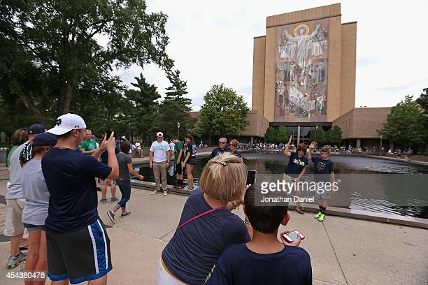 Fans take photographs in front of the mural at the Hesburgh Library commonly known as Touchdown Jesus before a game between the Norte Dame Fighting...