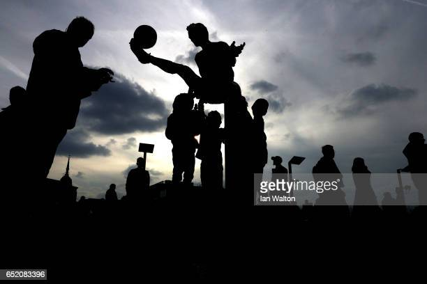 Fans take photographs of the Dennis Bergkamp statue outside the stadium prior to The Emirates FA Cup QuarterFinal match between Arsenal and Lincoln...