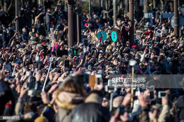 Fans take photos of Johnny Hallyday's funeral convoy accompanied by bikers on HarleyDavidson motorbikes as it arrives on the Place de la Concorde...
