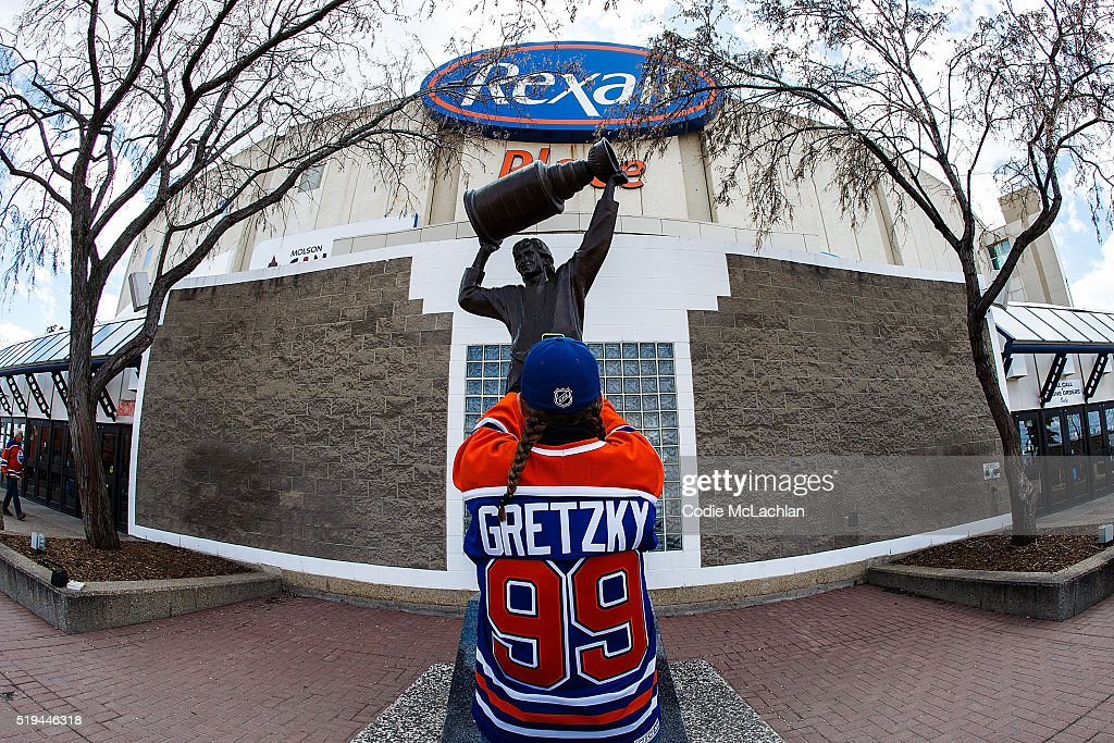 Fans take photos of the Wayne Gretzky statue outside of Rexall Place prior to the game between the Edmonton Oilers and the Vancouver Canucks on April 6, 2016 in Edmonton, Alberta, Canada. The game is the final game the Oilers will play at Rexall Place before moving to Rogers Place next season.