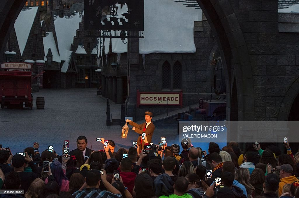 Fans take photos outside of Hogsmeade at the Grand Opening of the 'Wizarding World of Harry Potter' to the public at Universal Studios Hollywood, in Universal City, California, on April 7, 2016. Fifteen years after Harry Potter's first big screen adventure, Universal is enchanting a new generation of Muggles with its most spectacular conjuring trick yet -- a theme park in the heart of Hollywood. / AFP / VALERIE