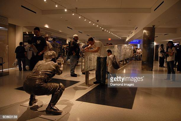 Fans take pictures and look at the collection of autographed baseballs mounted within the case that stands under the arc of the path of the final...