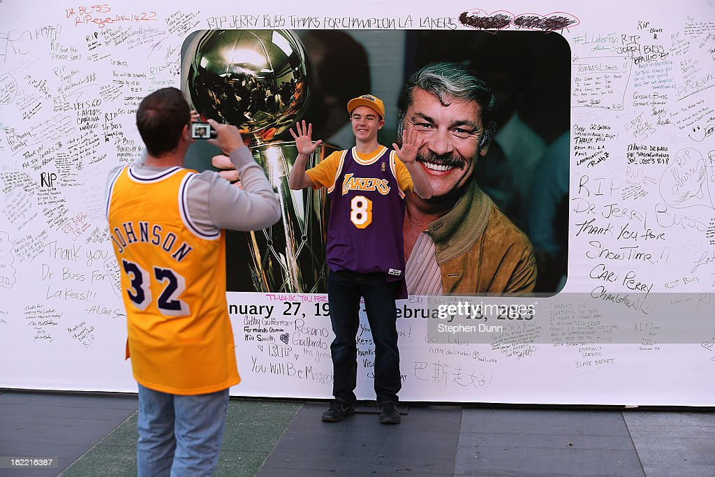 Fans take pictures in front of a wall near Staples Center in honor of the late Dr. Jerry Buss, owner of the Los Angeles Lakers, before the game against the Boston Celtics on February 20, 2013 in Los Angeles, California.