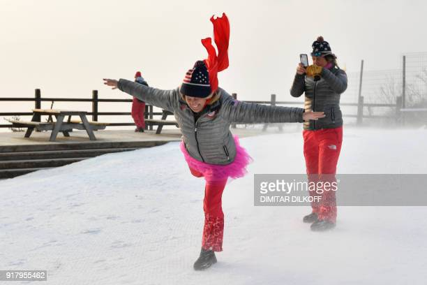 TOPSHOT US fans take pictures in the wind as the start of the Alpine Skiing Women's Slalom was delayed due to weather conditions at the Jeongseon...