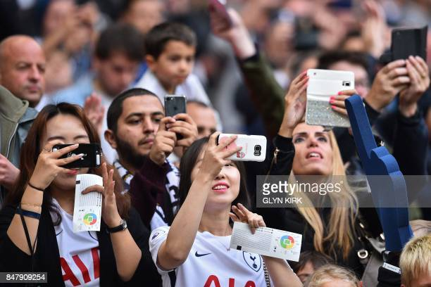 Fans take pictures of the teams coming out ahead of the English Premier League football match between Tottenham Hotspur and Swansea City at Wembley...