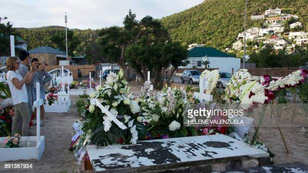 Fans take pictures of the tomb of late French music icon Johnny Hallyday on the French Caribbean island of SaintBarthelemy on December 12 a day after...