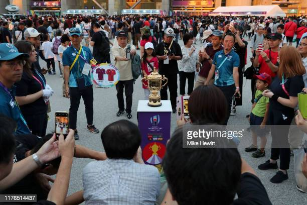 Fans take pictures of the Webb Ellis Cup outside the stadium prior to the Rugby World Cup 2019 Group D game between Wales and Georgia at City of...