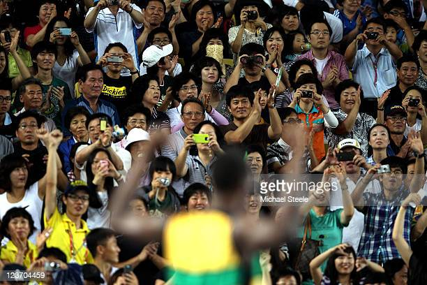 Fans take pictures of Usain Bolt of Jamaica following his victory and a new world record in the men's 4x100 metres relay final during day nine of...