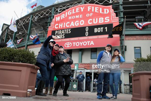 Fans take pictures outside of Wrigley Field during the Chicago Cubs home opener on April 10, 2018 in Chicago, Illinois. The game against the...