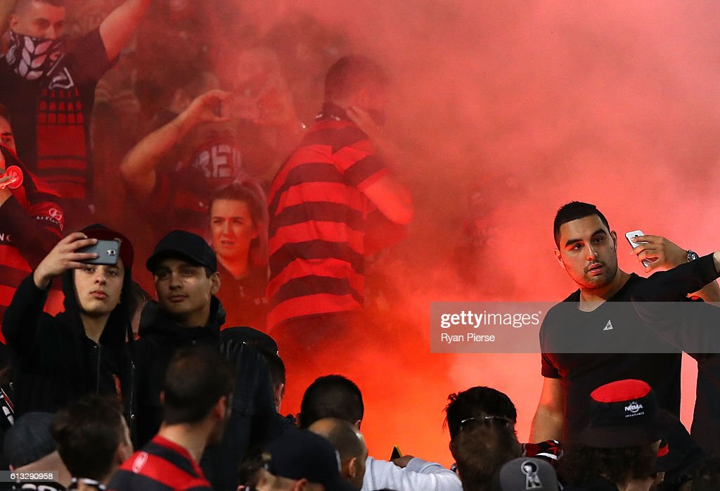 Fans take selfies as a flare is lit during the round one A-League match between the Western Sydney Wanderers and Sydney FC at ANZ Stadium on October 8, 2016 in Sydney, Australia.