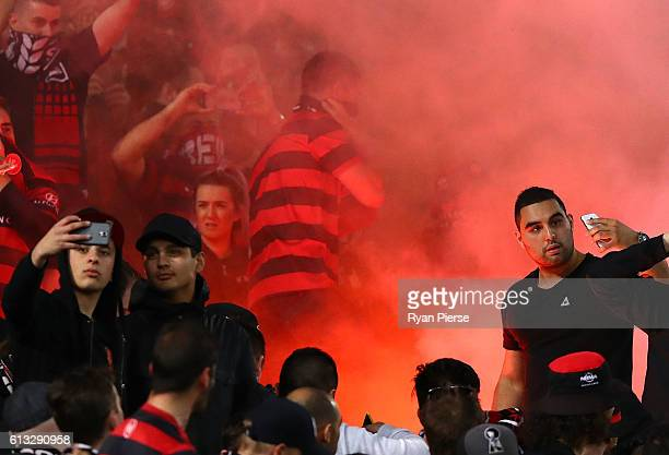 Fans take selfies as a flare is lit during the round one ALeague match between the Western Sydney Wanderers and Sydney FC at ANZ Stadium on October 8...