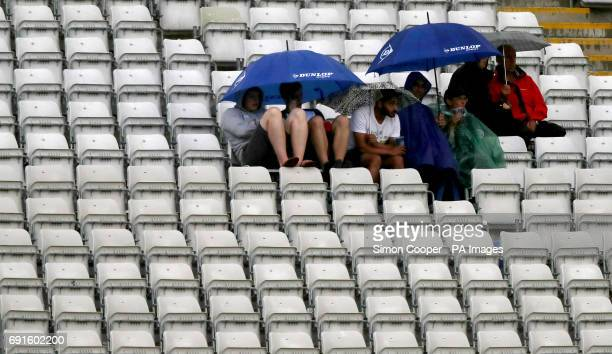 Fans take shelter as rain stops play during the ICC Champions Trophy Group A match at Edgbaston Birmingham