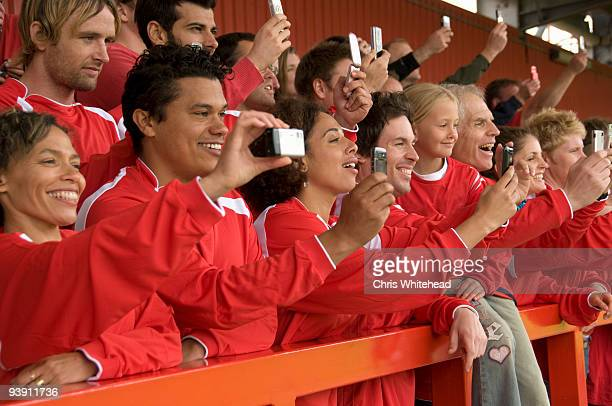 Fans taking photographs at football match