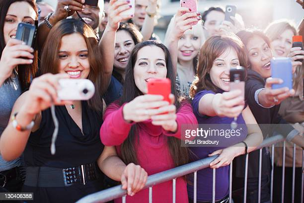 fans taking pictures with cell phone behind barrier - celebritet bildbanksfoton och bilder