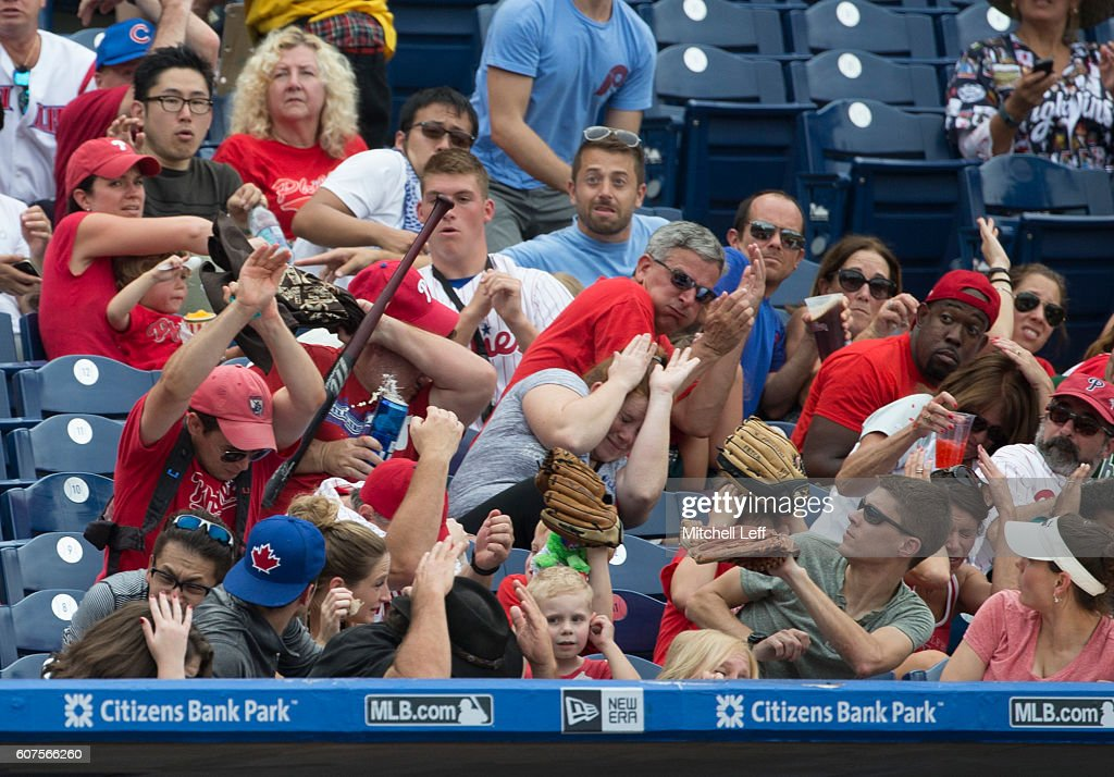 Fans try to avoid getting hit by a baseball bat that Jorge Alfaro #38 of the Philadelphia Phillies (NOT PICTURED) lost control of in the bottom of the sixth inning against the Miami Marlins at Citizens Bank Park on September 18, 2016 in Philadelphia, Pennsylvania. The Marlins defeated the Phillies 5-4.