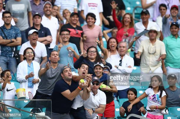 Fans try to catch a ball as SuWei Hsieh of Taipei plays against Naomi Osaka of Japan during the Miami Open Tennis on March 23 2019 in Miami Gardens...