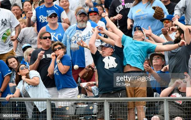 Fans try to catch a foul ball hit by Miguel Andujar of the New York Yankees in the fifth inning during a game against the Kansas City Royals at...