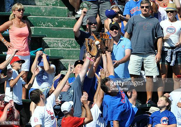 Fans try to catch a home run off the bat of Jon Jay of the St Louis Cardinals during the seventh inning against the Chicago Cubs on August 18 2013 at...