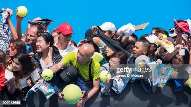 Fans try to get world number 2 Roger Federer to sign their merchandise on the practice court on day one of the 2018 Australian Open at Melbourne Park...