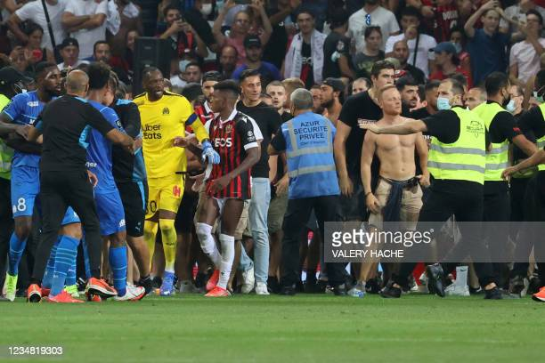 Fans try to invade the pitch during the French L1 football match between OGC Nice and Olympique de Marseille at the Allianz Riviera stadium in Nice,...