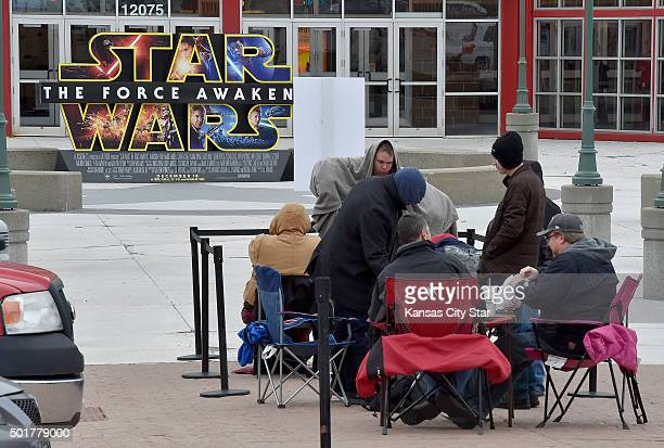 Fans try to stay warm as they wait in line for Star Wars The Force Awakens outside the AMC 28 Theater in Olathe Kan on Thursday Dec 17 2015