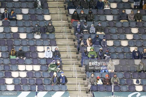 Fans try to stay warm while also wearing masks and social distancing in the first half of an MLS match between the Colorado Rapids and Sporting...