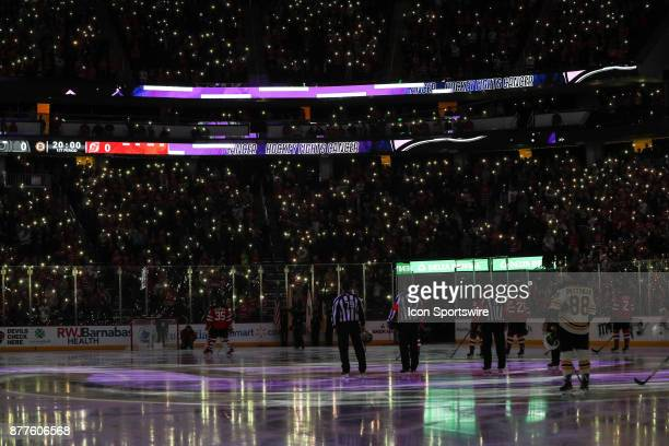 Fans turn on their phone flashlights during a moment of silence for Hockey Fights Cancer prior to the National Hockey League game between the New...