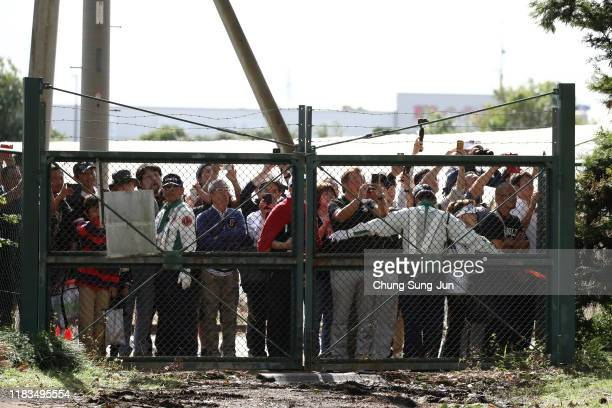 Fans unable to give up watching gather at a gate as no spectators are allowed to enter for safety measures during the second round of the Zozo...
