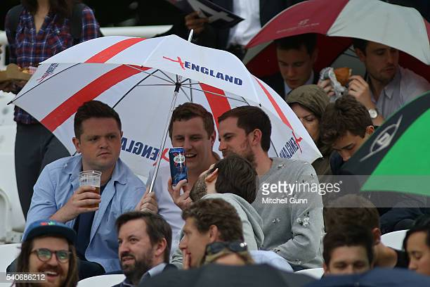 Fans under an umbrella during a rain shower before the start of play at the NatWest T20 Blast match between Middlesex and Sussex at Lords Cricket...