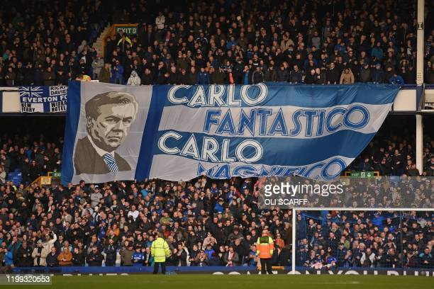 Fans unfurl a huge flag of Everton's Italian head coach Carlo Ancelotti in the crowd ahead of the English Premier League football match between...