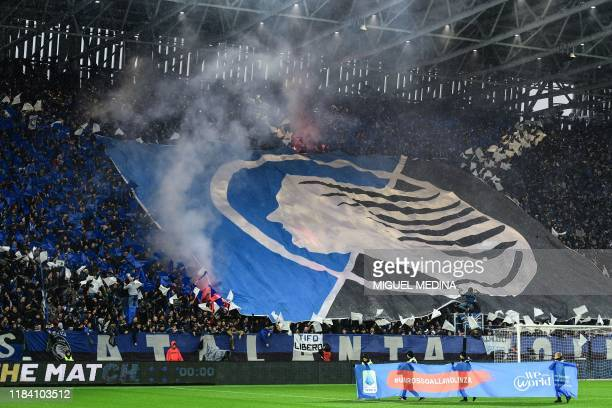 Fans unfurl a huge tifo as children hold a banner reading A Red Card to Violence and WeWorld Onlus with children with women for their rights against...