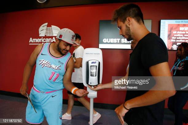 Fans use a hand sanitizer kiosk at the entrance of American Airlines Arena prior to the game between the Miami Heat and the Charlotte Hornets on...