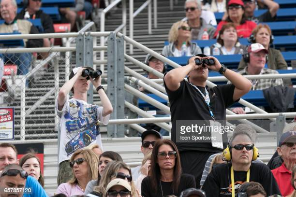 Fans use binoculars to watch the action on the track during the Xfinity Series 19th Annual Service King 300 at Auto Club Speedway in Fontana...