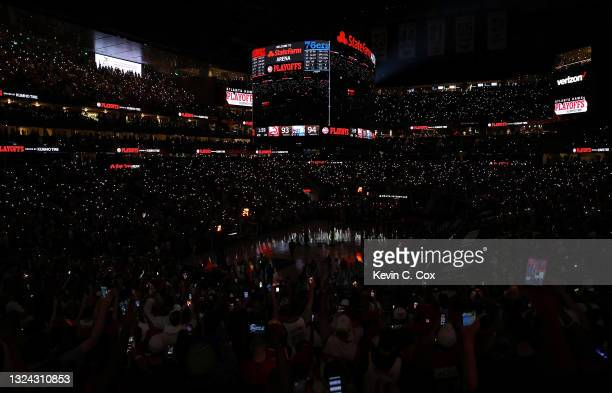 Fans use their cell phones to light the court after the lights went out as play resumed with just under two minutes left in the fourth quarter in...