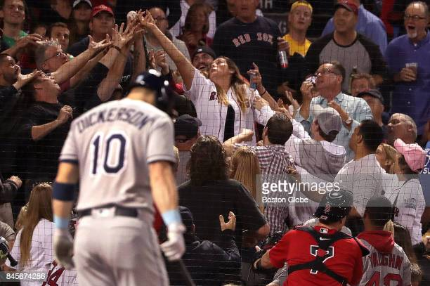Fans vie for a foul ball off the bat of Tampa Bay Rays left fielder Corey Dickerson that fell out of reach of Boston Red Sox catcher Christian...