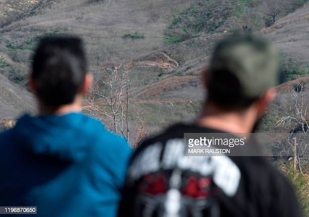 Fans view the helicopter crash site where the NBA legend Kobe Bryant died in Calabasas California on January 27 2020 after the crash that killed 9...