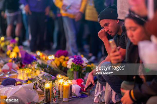 Fans visit a makeshift memorial near Staples Center in remembrance of former NBA great Kobe Bryant who along with his 13yearold daughter Gianna died...