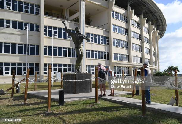 Fans visit the Sir Vivian Richards statue before Day Two of the 2nd Test match between West Indies and England at Sir Vivian Richards Stadium on...