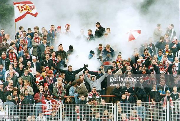 Fans vom 1.FC Union Berlin auf der Tribüne im Stadion Alte Försterei während eine Rauchbombe zwischen ihnen explodiert