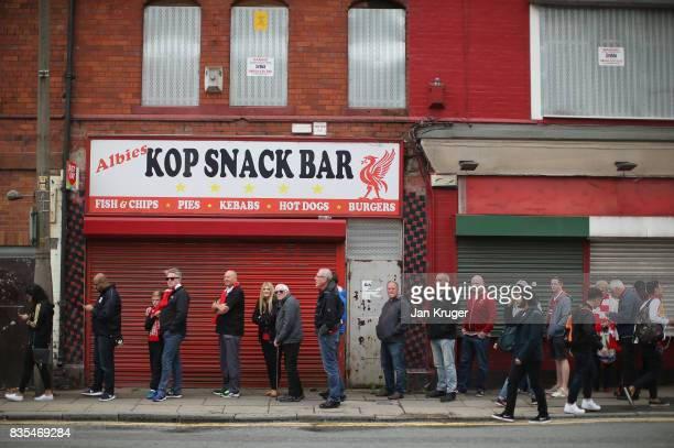 Fans wait for some pre match food prior to during the Premier League match between Liverpool and Crystal Palace at Anfield on August 19 2017 in...
