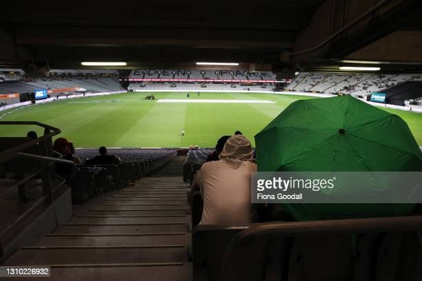 Fans wait for the rain to stop during game three of the International T20 series between New Zealand and Bangladesh at Eden Park on April 01, 2021 in...